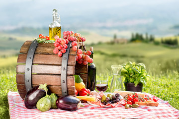 Lots of tasty italian food on the napkin and wooden barrel outdoors on the tuscany landscape background