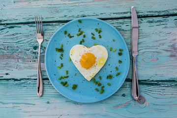 Tasty fried egg in the shape of a heart served on a plate on wooden table.