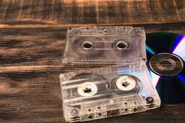 vinyl disc and cassette tapes on the wooden table.
