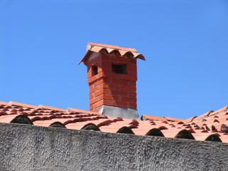 Brick chimney on the house with a tiled roof