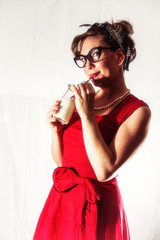 Lady in Red Drinking Milk Vintage. Lady in red drinking milk from a classic glass bottle and striped straw. Edited in a vintage film style.