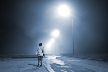 young man standing on the road in the fog near the forest. blue toning