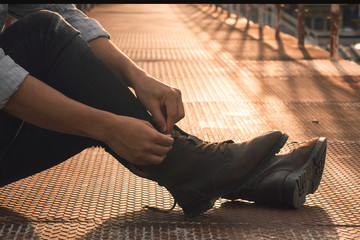 Man's hands tying shoes, Brown leather boots on a bridge at sunset, Men fashion.Toned picture