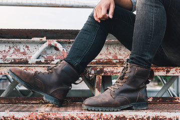 Close up view on man's legs in black jeans and brown leather boots on a bridge at sunset, Men fashion. Toned picture.
