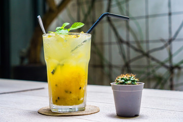 Yellow Sparkling Drink : Passion fruit-Mango Soda to quench your thirst on the wooden table with small Cactus decoration
