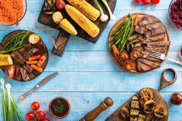 Grilled beef steak with grilled vegetables on wooden blue table