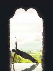 Silhouette young woman practicing yoga on the temple at sunset -