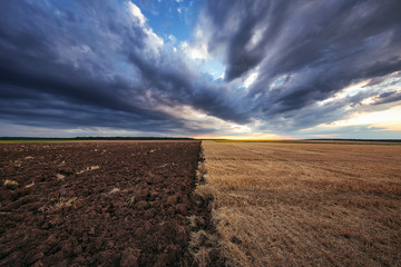 Dramatic clouds over the field after harvest