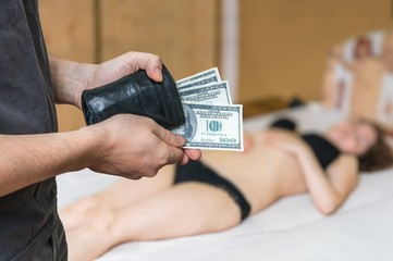 Man is paying with dollars a young prostitution for her work.