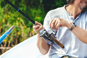Hands fisherman holding fishing rod and reel handle is rotated