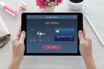 woman hands holding tablet computer with online air ticket scree