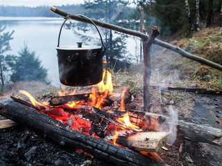 Cooking on the fire for a camping trip. Pot over a fire outdoors. The romance of the wild tourism and food in camp. Backpacking on the nature at sunset.