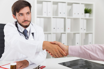 Serious doctor shaking hands with patient