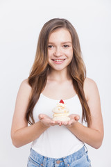Girl in jeans holding cupcake