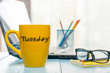 Tuesday written on yellow coffee or tea cup at wooden boards table, workplace, office sunlight morning background