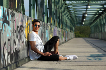 Handsome man with sunglasses sitting on a bridge with graffiti
