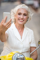 Smiling lady looks at phone. Mature woman with happy face. How do i look. Selfies during vacation.