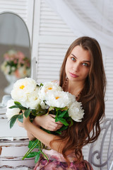 Beautiful girl with a bouquet of white flowers