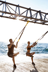 Young sportive people training with trx near sea in the morning.
