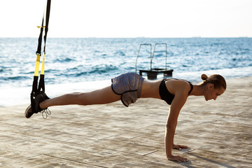 Young sportive girl training with trx near sea in the morning.