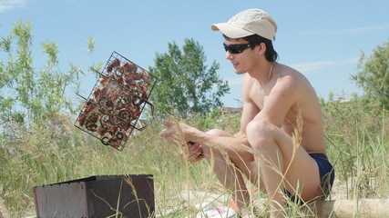Young man in sunglasses fry the meat on the beach near the sea. Hot food Shashlik in Russia.
