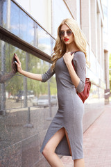 Fashion portrait of young elegant blond woman outdoor.