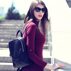 Fashion portrait of young elegant brunette woman outdoor.