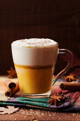 Pumpkin spiced latte or coffee in a glass on a wooden table. Autumn or winter hot drink.