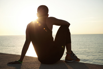 Back shot of dark-skinned runner with muscular athlete body sitting on pavement at ocean, contemplating sunset over sea resting elbow on his knees while having break after hard working day in office
