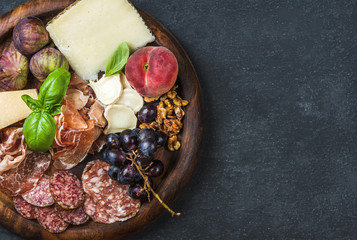 Italian antipasti snack for wine. Prosciutto di Parma, salami, cheese variety, figs, grapes, peach, walnuts and fresh basil on wooden serving tray over dark grunge background. Top view, copy space
