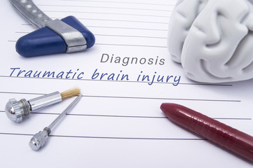 Figure of human brain, blue neurological reflex hammer, neurological needle and brush for test sensitivity and ballpoint pen lie on a paper form with a medical diagnosis of Traumatic brain injury