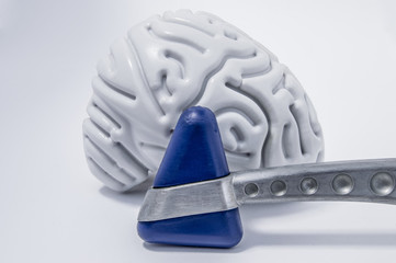 Neurological reflex hammer stands in front of the figure of the human brain on a white medical table front view. Concept pic for neurological or neuroscience surveys or examinations
