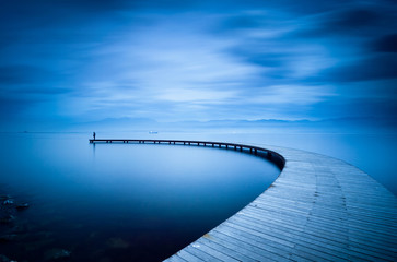 Young man looking to sea on curved jetty