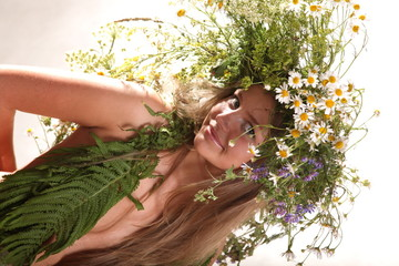 naked girl in a wreath of daisies and other flowers