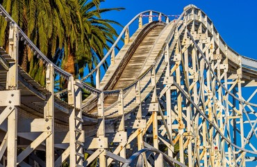 Old rollercoaster against sky and palm tree