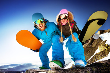 Happy couple of snowboarders stands on big rock. Mountains backdrop