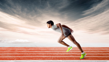 Side shot of a muscular latin runner learing strongly forward on orange track against dramatic sunset sky background