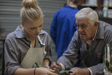 Instructor talking to trainee in workshop holding bronze cast piece