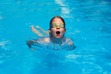 Child swims butterfly style in the pool