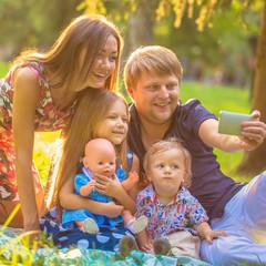 Happy family taking selfie  in park.