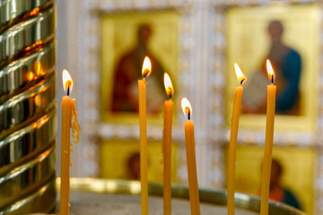 burning candles on the background of icons in the Orthodox Church.