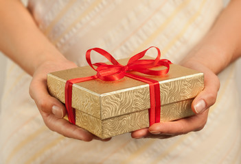 Close up shot of female hands holding a gift wrapped with red ri