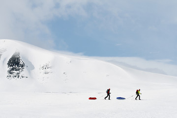 People doing cross-country skiing and pulling sledge