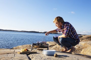 Man having grill on cliff, Bohuslan, Sweden