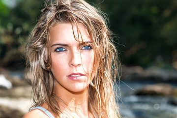 Portrait of beautiful blond girl with deep blue eyes with wet ha