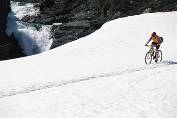 A man riding a bicycle in snow