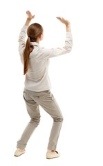 back view of woman protects hands from what is falling from above. Isolated over white background. Skinny girl in white denim suit holding a load over your head.