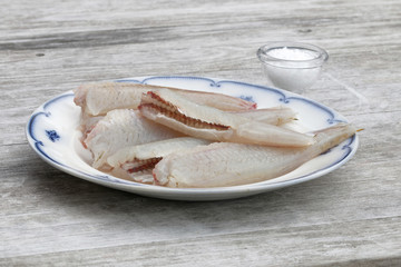 Gutted european bass fish laying on a blue and white plate