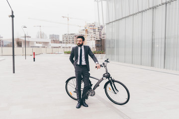 young casual bearded businessman riding a bike outdoor in the city - ecological, transport, business concept