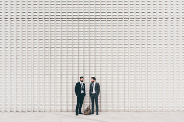 Two young contemporary caucasian bearded businessmen standing outdoor in front off a white wall - business, elegant, boss concept - copyspace